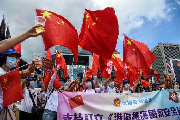 Pro-China supporters display Chinese and Hong Kong flags as they raise a toast with champagne during a rally near the government headquarters in Hong Kong on June 30, 2020, as China passed a sweeping national security law for the city. - China passed a sweeping national security law for Hong Kong, a historic move that critics and many western governments fear will smother the finance hub's freedoms and hollow out its autonomy. (Photo by Anthony WALLACE / AFP) (Photo by ANTHONY WALLACE/AFP via Getty Images)