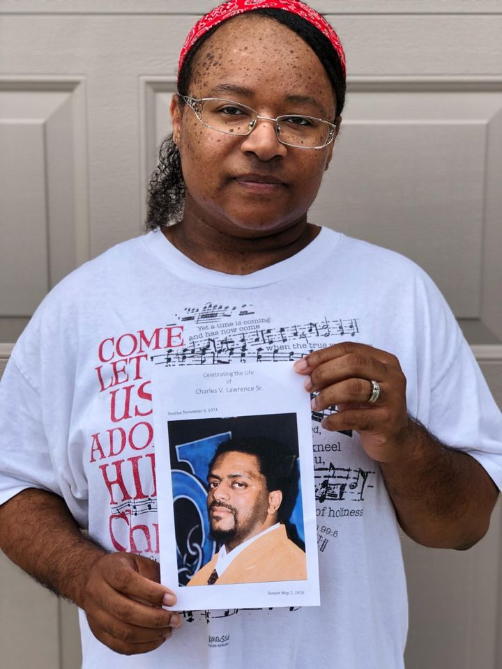 Sanya Lawrence holds a photo of her husband, Charles Lawrence, who died from the coronavirus in May 2020.