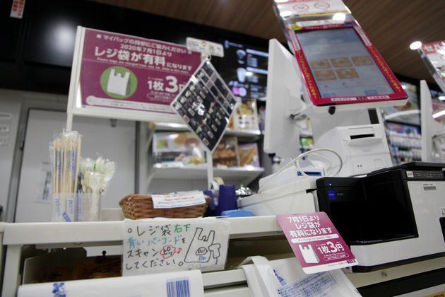 ポスターなどでレジ袋の有料化を周知するコンビニのレジ周辺=7月1日午前、東京都品川区