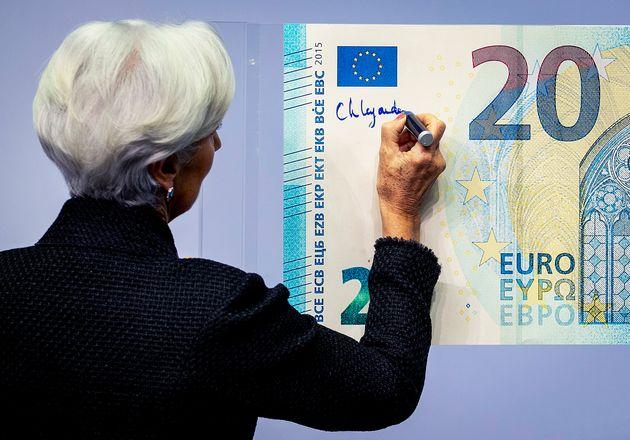La nueva presidenta del Banco Central Europeo, Christine Lagarde, agrega su firma a un billete de euro de tamaño exagerado en la sede del BCE en Fráncfort, Alemania, miércoles 27 de noviembre de 2019. (AP Foto/Michael Probst)