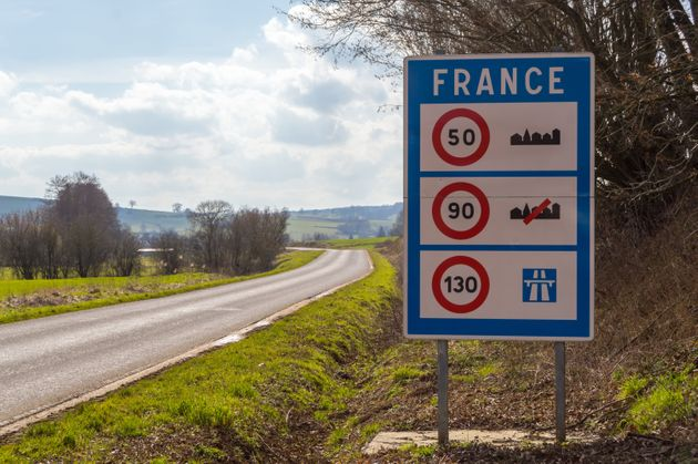 Road sign of return to the French territory with different speed limits along the