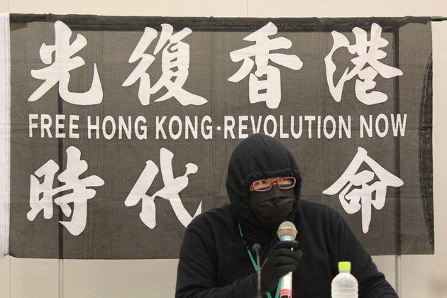 登壇した在日香港人。背後は「香港を取り戻せ、時代革命だ」