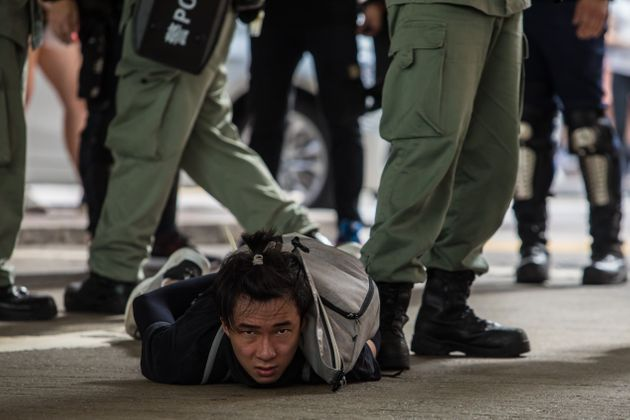 Riot police detain a man as they clear protesters taking part in a rally against a new national security...