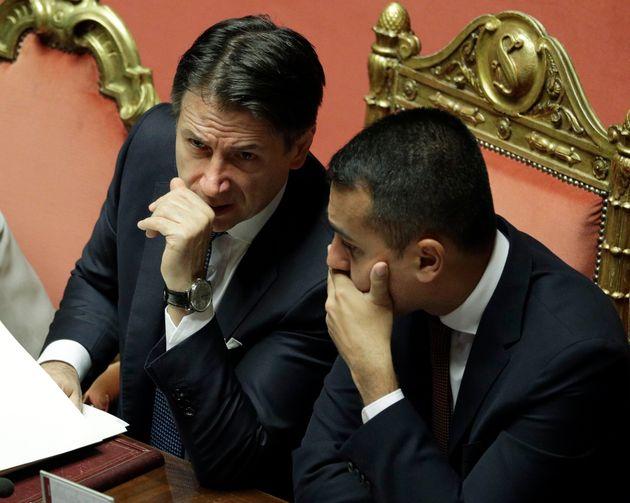 Italian Premier Giuseppe Conte, left, shares a word with Foreign Minister Luigi Di Maio at the Senate...