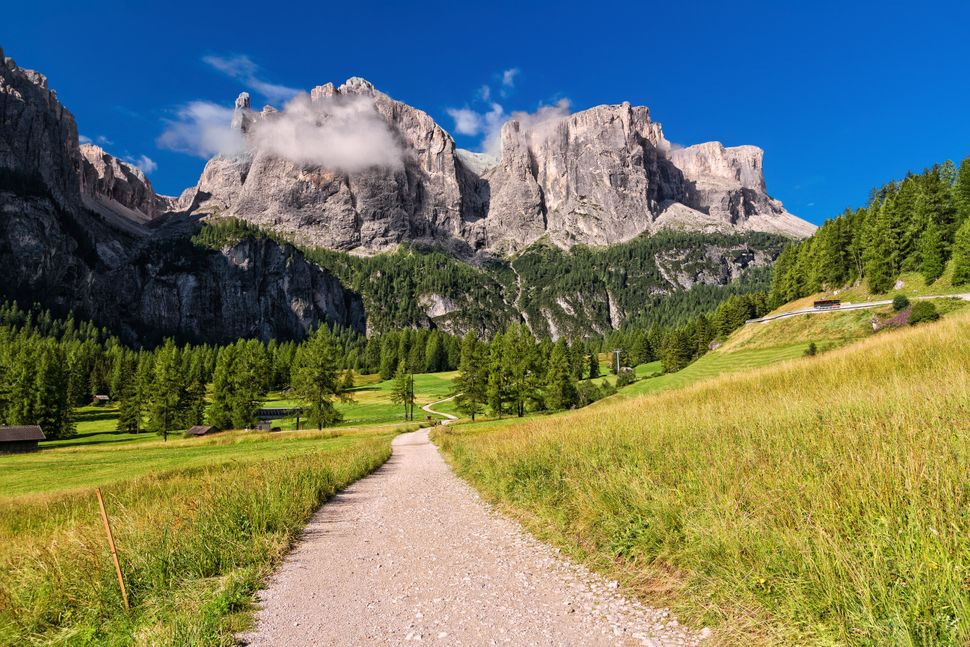 footpath in high Badia Valley, on background Sella mount, Alto Adige, Italy