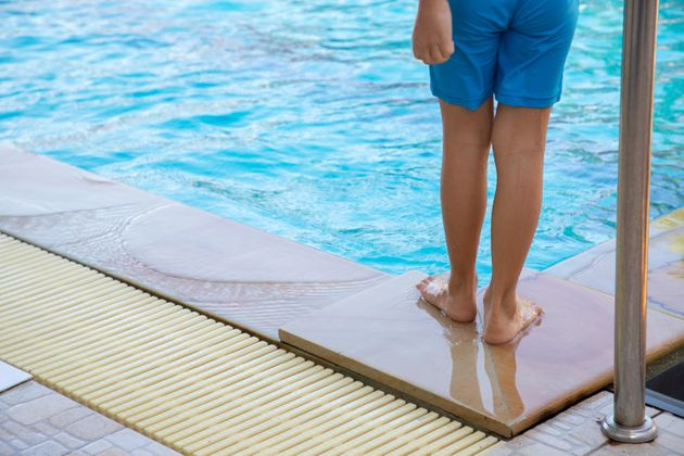 child swimmer standing pool side. concept of