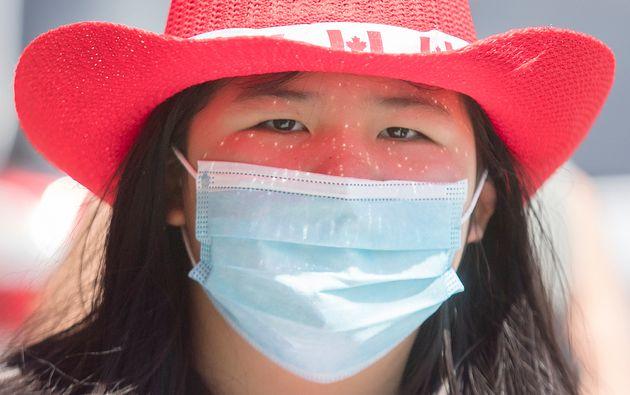 Une femme porte un masque et un chapeau à l'effigie du drapeau canadien, à