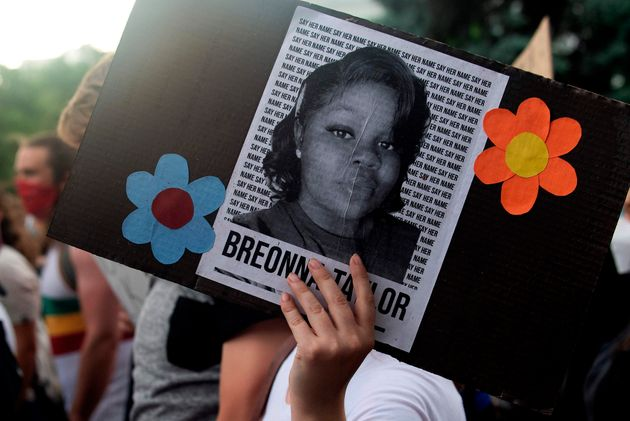 A demonstrator holds up the image of Breonna Taylor, a Black woman who was fatally shot by Louisville...