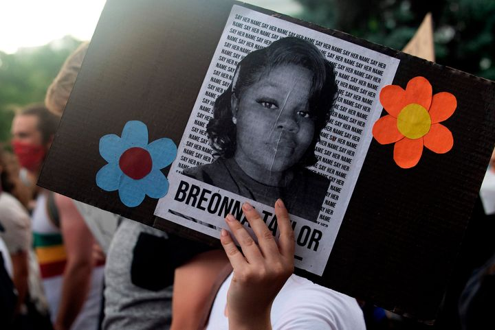 A demonstrator holds up the image of Breonna Taylor, a Black woman who was fatally shot by Louisville police officers, during