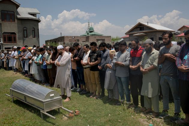 Relatives and neighbors offer prayers near the coffin of civilian Bashir Ahmed Khan, during his funeral...