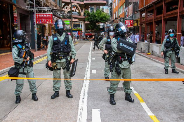 Police stand behind the cordon line during street rallies in Causeway Bay, Hong Kong, China on July 1,...