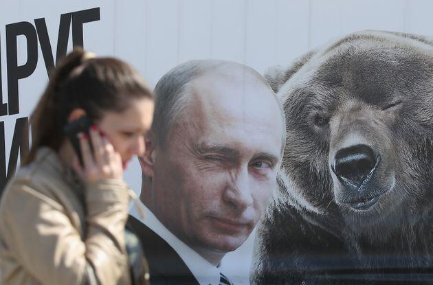 한 여성이 윙크하는 블라디미르 푸틴 러시아 대통령의 초상화와 곰의 그림 앞을 지나가고 있다. 2015. 5.