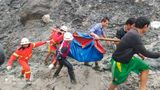 In this photo released from Myanmar Fire Service Department, rescuers carry a recovered body of a victim in a landslide from a jade mining area in Hpakant, Kachin state, northern Myanmar Thursday, July 2, 2020. Myanmar government says a landslide at a jade mine has killed dozens of people. (Myanmar Fire Service Department via AP)