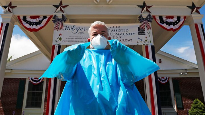 Brendan Williams, president of the New Hampshire Health Care Association, wears an isolation gown with no sleeve openings for