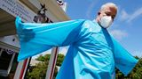 Brendan Williams, president of the New Hampshire Health Care Association, wears an isolation gown with no sleeve openings for hands, which was received in a shipment from the federal government, outside Webster at Rye senior care center on Wednesday, July 1, 2020, in Rye, N. H. The problematic gowns, child-sized examination gloves and surgical masks with ear loops that break when stretched make up the bulk of the personal protective equipment recently sent by the Federal Emergency Management Agency to New Hampshire nursing homes, according to Williams. The facility is not using the items they received from FEMA. (AP Photo/Charles Krupa)