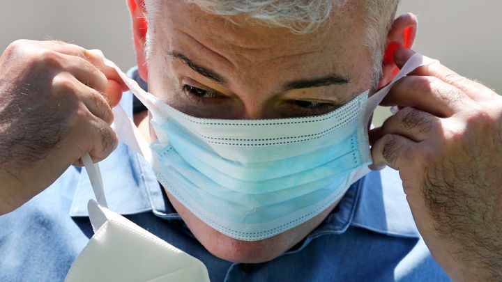 Williams stretches the thin cloth band of a surgical mask, provided by FEMA, over his face.
