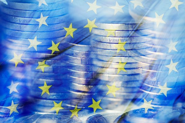 a multiple exposure of some piles of euro coins and a flag of the European
