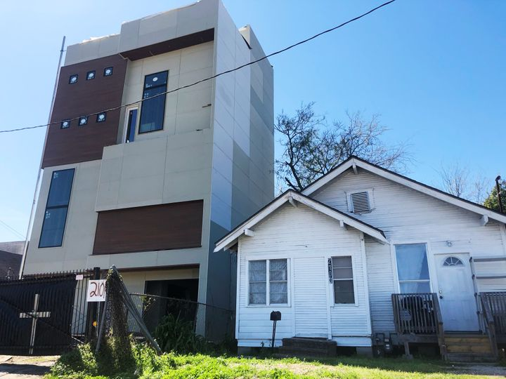 A newer apartment building built after Harvey (left) squeezes next to a pre-Harvey home in northeast Houston.