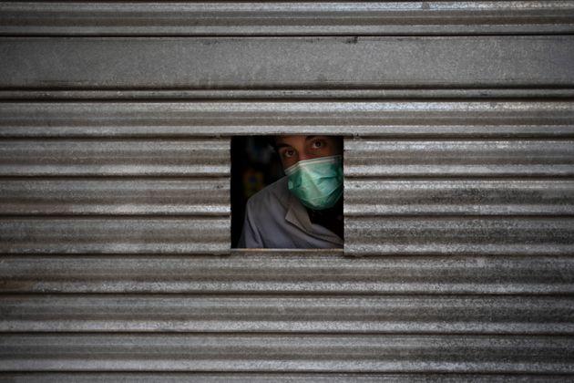 Un hombre se asoma por una pequeña abertura en una farmacia de