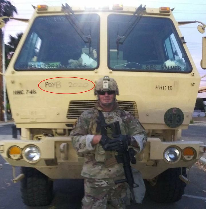 Sgt. Brian Jackson of the California National Guard posted this Facebook photo on June 2 while deployed to police Black Lives Matter protests in Los Angeles. It shows him standing in front of a military vehicle inscribed with a slogan for the Proud Boys, a neo-fascist group.