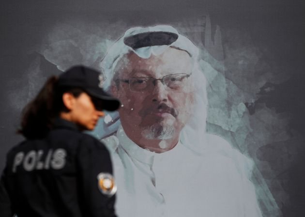 A Turkish police officer walks past a picture of slain Saudi journalist Jamal Khashoggi prior to a ceremony,...