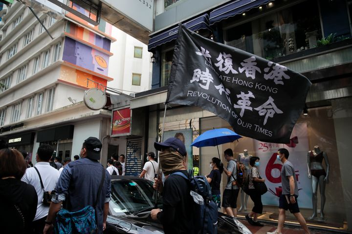 """Protesters carry the flag which reads """"Liberate Hong Kong, revolution of our time"""" in Causeway Bay before the annual handover"""