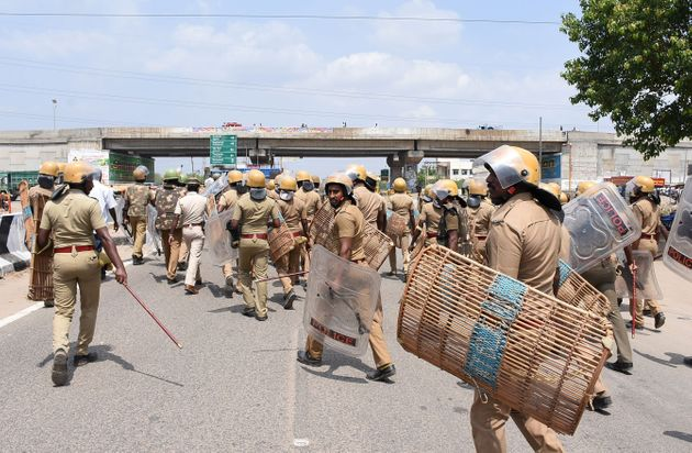 Indian police officials move towards protestors in Thoothukudi on May 22, 2018. Around 13 people were...
