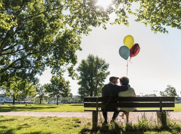 Happy senior couple with balloons sitting on bench in a park