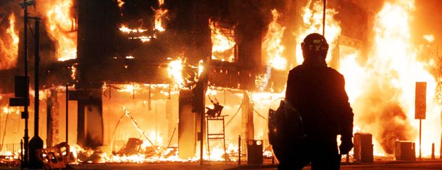 Riot police look on as fire rages through a building in Tottenham, north London, as trouble flared after...