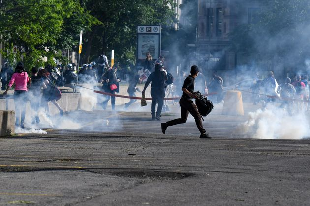 Demonstrators are running as Montreal Police uses tear gas during a march against police brutality and...
