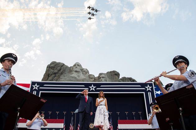 President Donald Trump, accompanied by first lady Melania Trump, stands during the national anthem with...