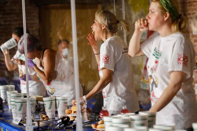 Competitive eater Miki Sudo, second right, eats a women's world record of 48 and a half hot dogs to win...