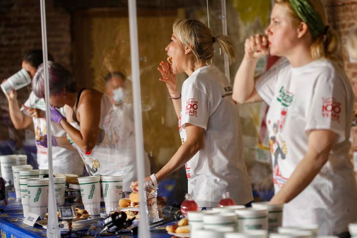Competitive eater Miki Sudo, second right, eats a women's world record of 48 and a half hot dogs to win the women's division