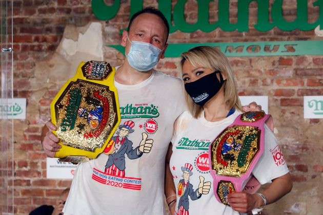Competitive eaters Joey Chestnut, left, and Miki Sudo, right, pose for a photograph after winning their...