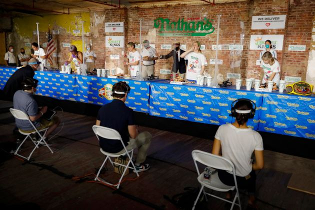 Competitors separated by translucent panels eat in the women's division of the Nathan's Famous July Fourth...