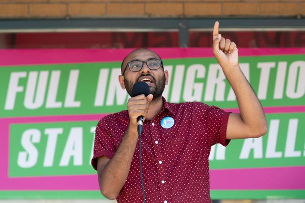 Syed Hussan, executive director of Migrant Workers Alliance for Change, speaks to a crowd gathered in...