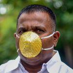 Un Indien porte un masque en or pour se protéger du
