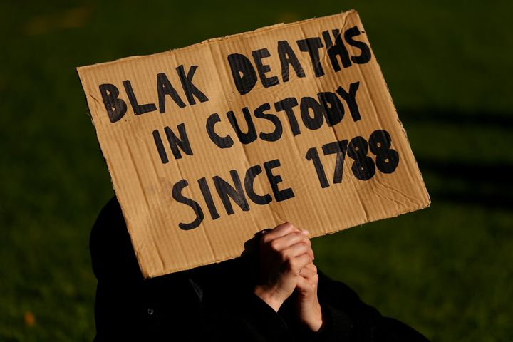 SYDNEY, AUSTRALIA - JULY 05: A man holds up a sign during a rally against Black Deaths in Custody in The Domain on July 05, 2020 in Sydney, Australia.The rally was organised to protest against Aboriginal and Torres Strait Islander deaths in custody and in solidarity with the global Black Lives Matter movement. (Photo by Don Arnold/Getty Images)