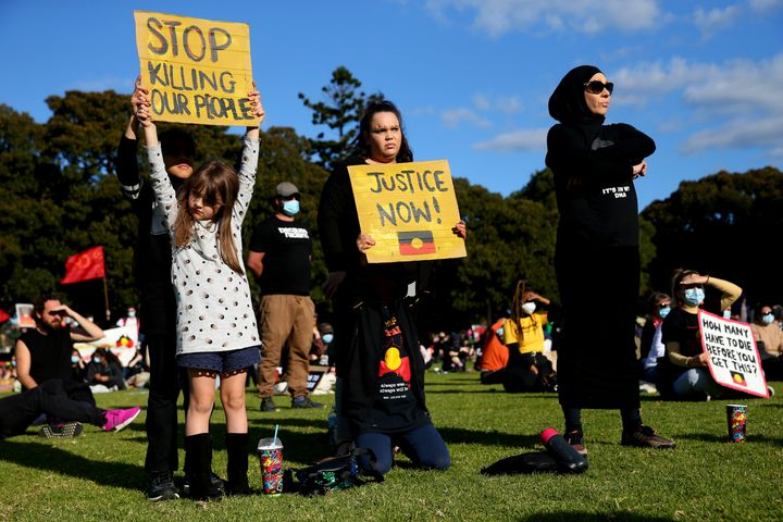 SYDNEY, AUSTRALIA - JULY 05: People hold up signs during a rally against Black Deaths in Custody in The Domain on July 05, 2020 in Sydney, Australia.The rally was organised to protest against Aboriginal and Torres Strait Islander deaths in custody and in solidarity with the global Black Lives Matter movement. (Photo by Don Arnold/Getty Images)