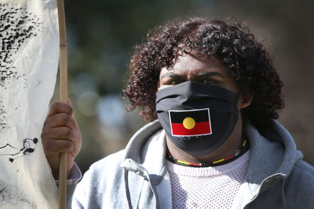 SYDNEY, AUSTRALIA - JULY 05: A protester wears a face mask depicting the Aboriginal Flag during a rally...