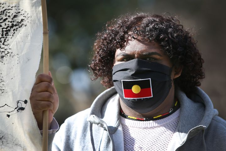 SYDNEY, AUSTRALIA - JULY 05: A protester wears a face mask depicting the Aboriginal Flag during a rally against Aboriginal and Torres Strait Islander deaths in custody in The Domain on July 05, 2020 in Sydney, Australia. Since the Royal Commission into Aboriginal deaths in custody ended in 1991 there have been over 400 deaths. Rallies have been organised across the country in solidarity with the global Black Lives Matter movement. (Photo by Lisa Maree Williams/Getty Images)