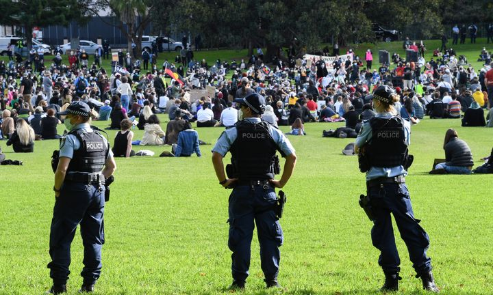 SYDNEY, AUSTRALIA - JULY 05: Police wear face masks as they watch people gather in the Domain on July 05, 2020 in Sydney, Australia. The rally was organised to protest against Aboriginal and Torres Strait Islander deaths in custody and in solidarity with the global Black Lives Matter movement. (Photo by James D. Morgan/Getty Images)