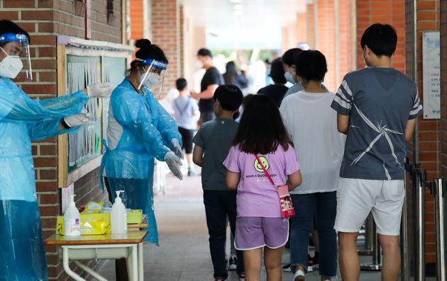 서울 중랑구의 묵현초등학교 학생 1명이 신종 코로나바이러스 감염증(코로나19) 확진 판정을 받은 5일 묵현초에 마련된 선별진료소에서 학생들이 전수검사를 기다리고