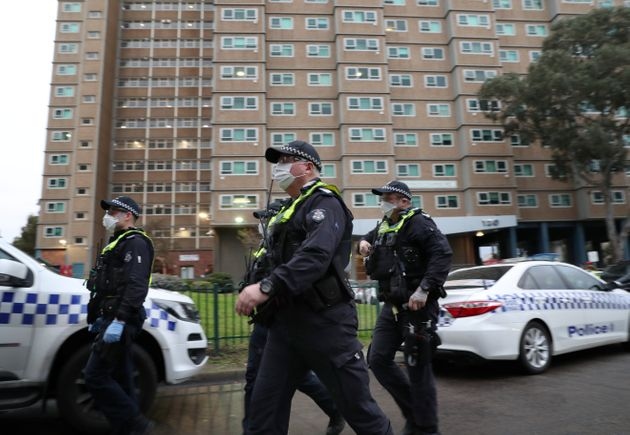 Police officers walk as they enforce a lockdown in response to an outbreak of coronavirus in