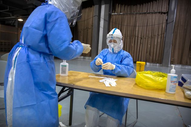 Workers in protective suits prepare to administer a coronavirus test at a testing site in Beijing on...