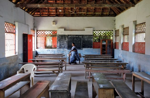 A staff member walks inside an empty classroom of a school after Kerala government ordered the closure...