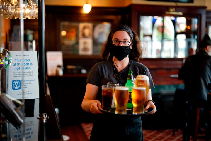 A member of bar staff wearing a face mask carries drinks inside the Wetherspoon pub, Goldengrove in Stratford in east London,