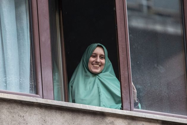 Silvia Romano smiles from a window after she arrived at her home, in Milan, Italy, Monday, May 11, 2020....