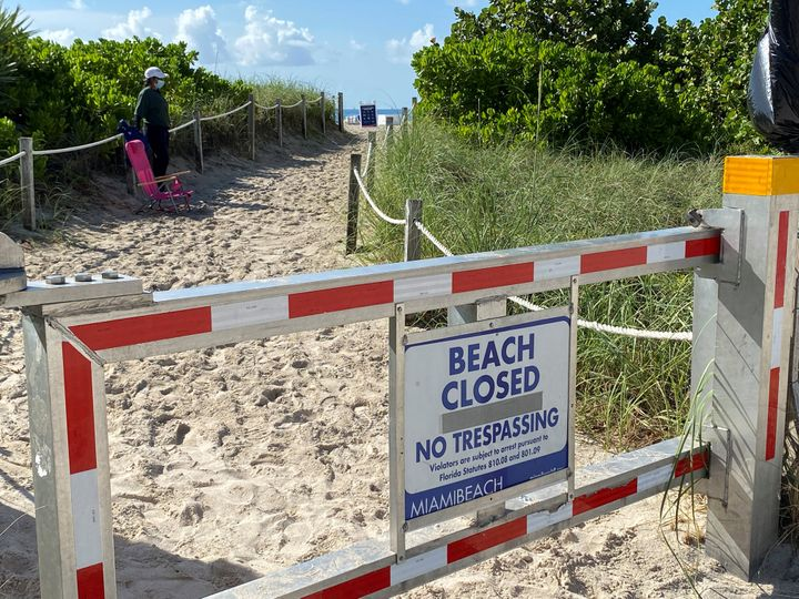 A sign announces beach closure to prevent the spread of the coronavirus ahead of the Fourth of July weekend in Miami Beach, Florida.