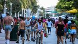 A man rides a bicycle as people walk on Ocean Drive in Miami Beach, Florida on June 26, 2020. - They are itching for a good time after months of lockdown, and may the coronavirus be damned: young adults in Florida are fueling a dangerous rise in COVID-19 infections. Feeling immortal, these fun-crazed people are finding ways to gather and party even though many bars and nightclubs remain closed as the Sunshine State reopened its economy this month. (Photo by CHANDAN KHANNA / AFP) (Photo by CHANDAN KHANNA/AFP via Getty Images)